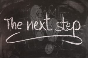 """a black board with chalk footprints. Over these are the words """"the next step"""" in chalk"""