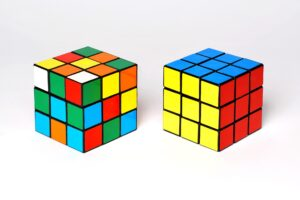 two Rubik's cubes; the one of the right is solved and the one on the right isn't