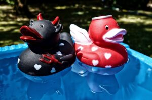 two rubber duckies, one styled like an angel and the other styled like a devil, floating atop water