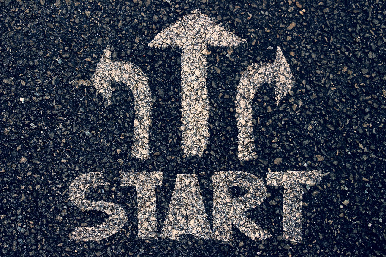 The word start painted on a road, with arrows pointing ahead, to the left, and to the right