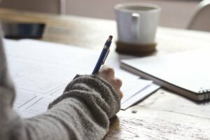 a hand holding a pen on top of paper sitting on a desk with a mug of coffee sitting also on the table in the background