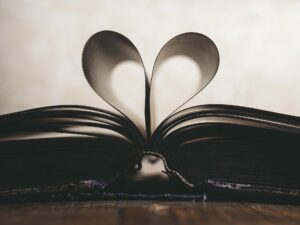 an open book with two pages bent to make a heart shape