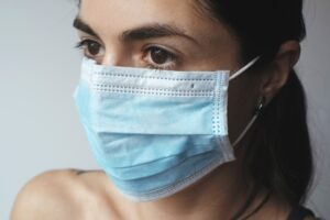 a person wearing a blue surgical face mask