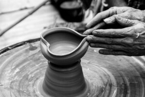 a black and white photo of hands shaping a piece on a pottery wheel