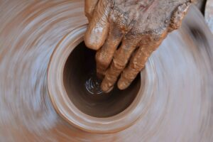 a photo of someone opening a piece of a clay on the pottery wheel