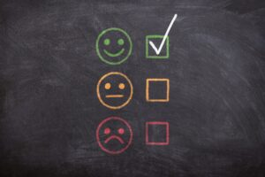 a chalkboard with a green happy face, yellow neutral face, and a red frowning face. There are checkboxes next to each of these three faces. The smiling face box is checked.