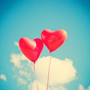 two red heart balloons floating in a blue sky with clouds
