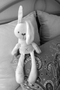 black and white stuffed bunny on a bed