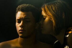 one person whispering into the ear of another in semi-darkness