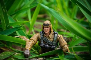 a plastic toy soldier moving through the grass
