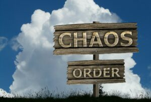 a signpost with two labeled signs, the top one says Chaos, and the bottom one says Order